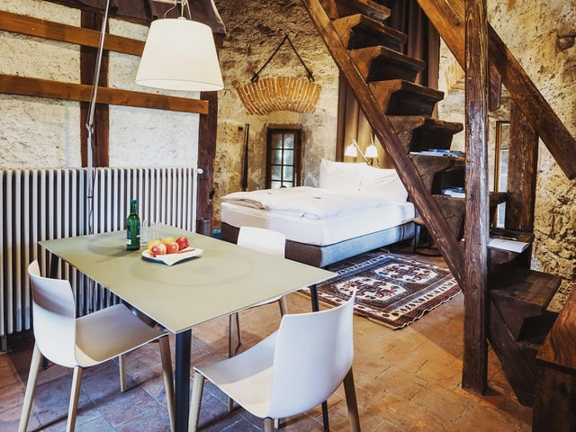 Ein Zimmer mit Tisch und Bett in einem alten Gebäude