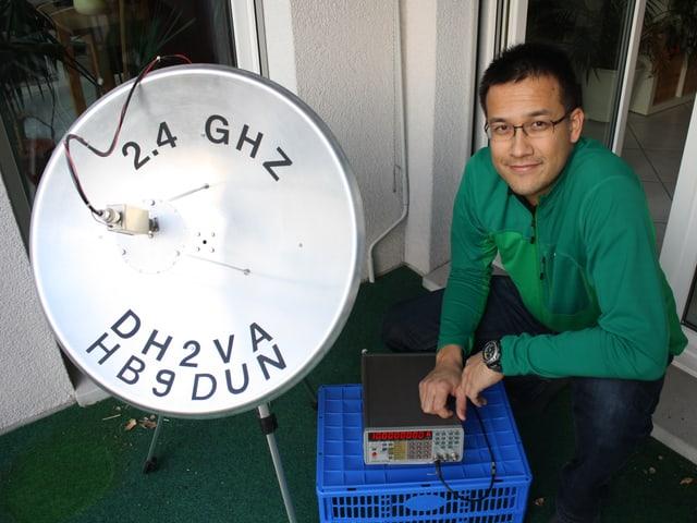Achim Vollhardt hockt in grünem Pullover auf einem Balkon, links neben ihm eine Satellitenschüssel.