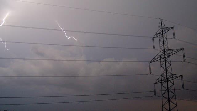 Strommasten, Stromleitungen am Himmel, im Hintergrund ein Gewitter mit Blitzen.