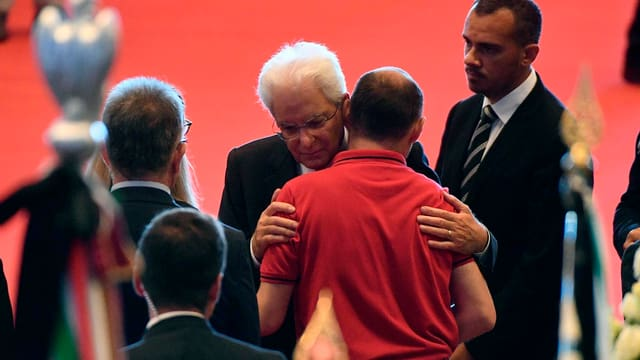 Mann mit weissen Haaren (Mattarella) umarmt anderen Mann.