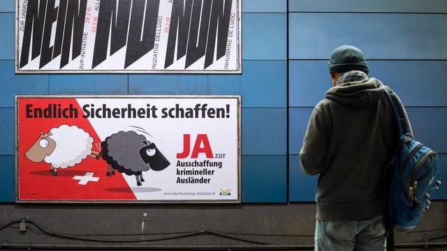 Ein Mann vor einem SVP-Plakat zur Durchsetzungsinitiative.