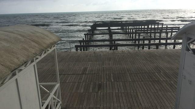 Im Vordergrund die Strandhäuschen auf einer mit Holz bedeckten Plattform, dahinter aus dem Meer ragende Holzpfähle.