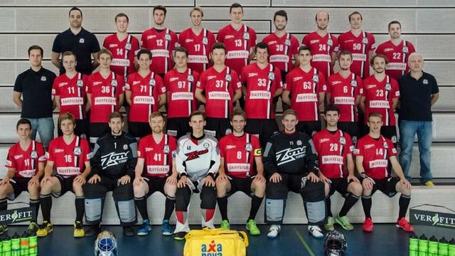 Die Spieler von Unihockey Basel Regio sitzen und stehen in drei Reihen hintereinander. Das T-Shirt ist rot, die Hosen schwarz.