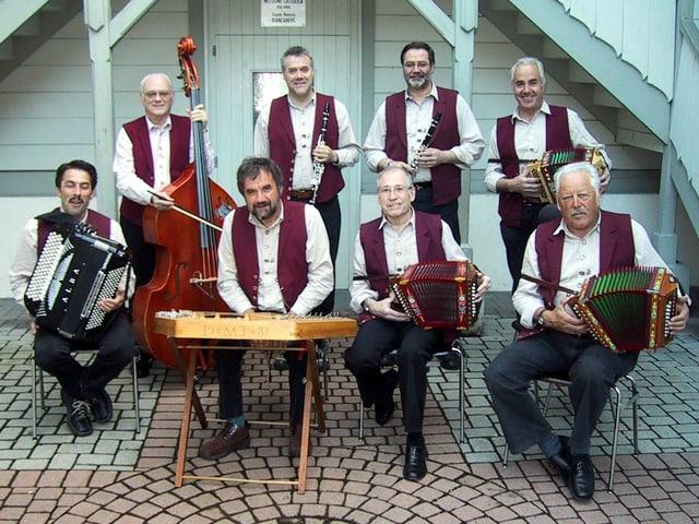 Acht Musikanten mit ihren Instrumenten auf dem Gruppenfoto vor einem weissen Holzhaus.