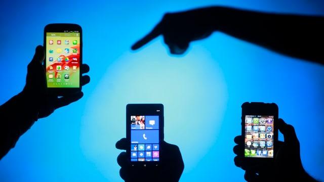 Symbolbild: Drei Smartphones vor blauem Hintergrund