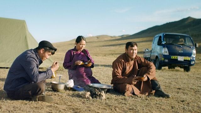 Drei Personen essen in der Steppe