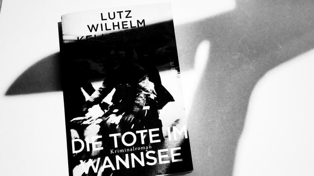 Der Krimi «Die Tote im Wannsee» liegt am Boden, darüber sieht man den Schatten eines Messers