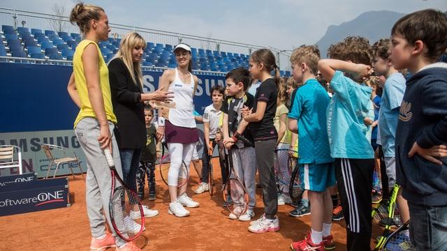Kinder hören drei Tennisspielerinnen zu.