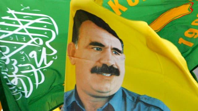Fahnen mit dem Portrait von Öcalan an einer Demonstration in Deutschland.