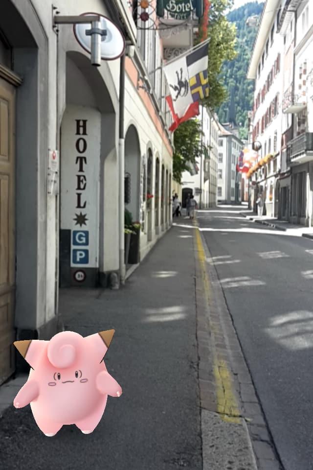 In maletg da computer dad in pokemon pitschen radund rosa cun duas ureglias da piz, combas curtas e bratscha fitg curta. Davostiers ina foto 'reala' da la Reichsgasse a Cuira.