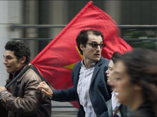Filmstill: Junge Menschen rennen durch die Strasse, einer trägt eine rote Flagge.