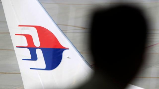 Silhouette eines Kopfes vor einem Flugzeug der Malaysian Airlines