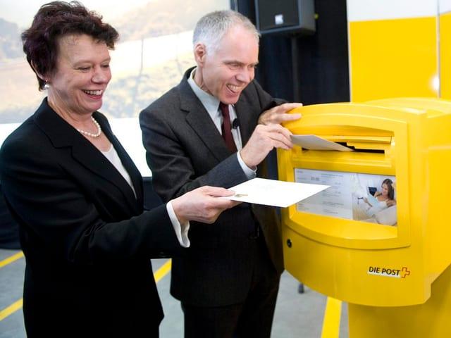 Politiker werfen Brief in einen gelben Briefkasten ein