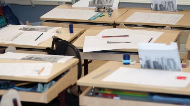 Leere Pulte auf denen Zettel und Schreibgeräte liegen.