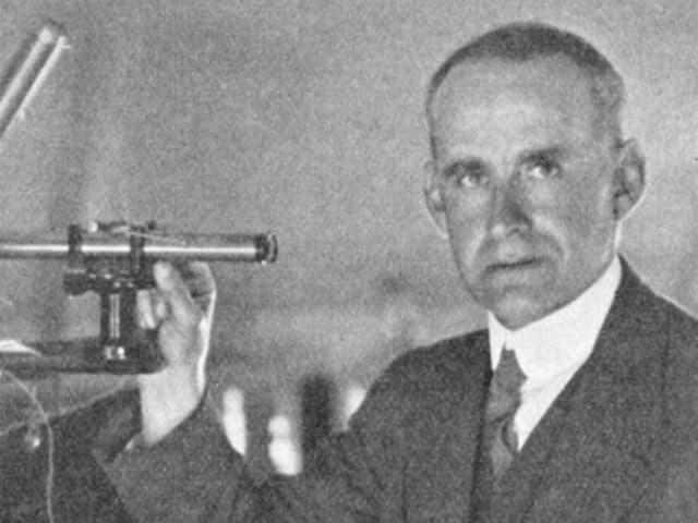 Schwarzweiss-Bild eines Mannes mit einem astronomischen Instrument in der Hand
