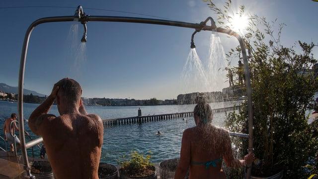 Zwei Personen duschen in Badehose bei strahlendem Sonnenschein