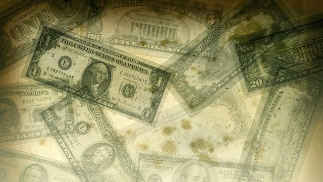 US-Dollarnoten liegen verstreut da, zum Teil mit Schmutzflecken bedeckt.
