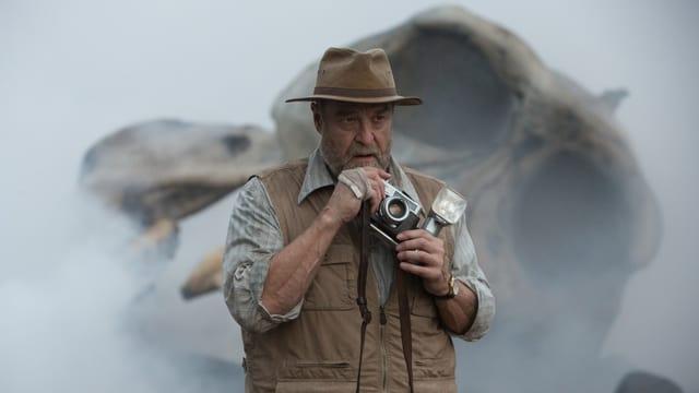 Ein Mann mit Kamera steht vor einem mannshohen Gorillaschädel.