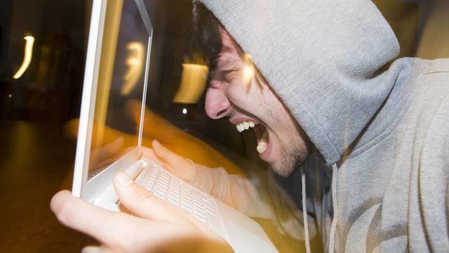 Ein Mann mit Kapuze brüllt in seinen Laptop.