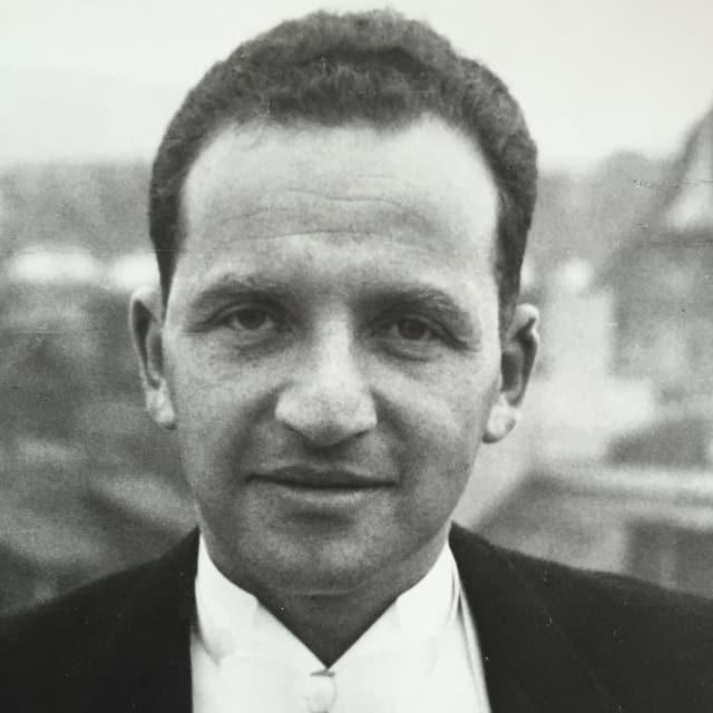Alte schwarz-weiss-Fotografie: ein Mann mittleren Alters mit dunklen Haaren im Anzug.