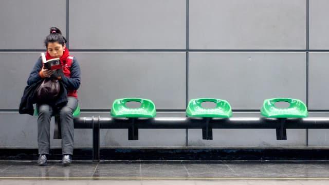 Frau sitzt auf einer Bank in einer U-Bahn-Haltestelle. Neben ihr sind drei Plätze frei.