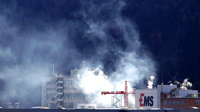 Ansicht des EMS-Firmengeländes. Dicke weisse Nebel stehen über den Gebäuden.