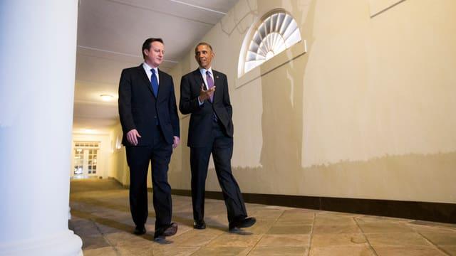 Obama und Cameron schlendern durch einen Gang.