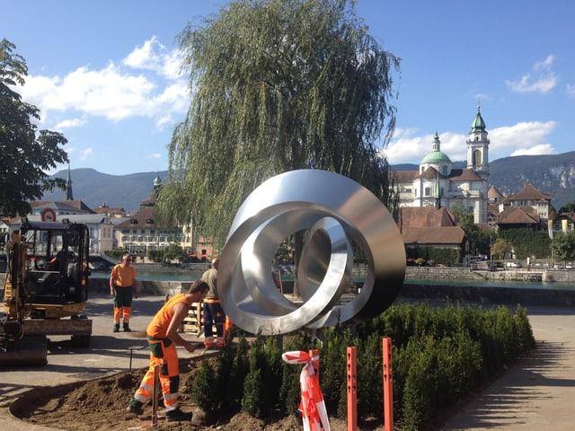 Arbeiter bauen Skulptur auf