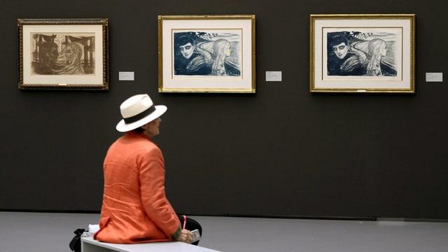 Eine Ausstellungsbesucherin sitzt vor drei Munch-Bildern im Kunsthaus Zürich