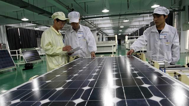 Chinesische Arbeiter vor einem Solarmodul