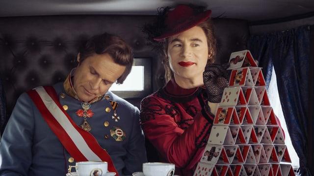 Tramitz als schlafender Kaiser in der Kutsche, Bully daneben als Kaiserin Sissi, sie baut ein Kartenhaus