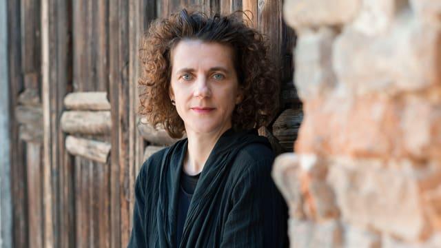 Porträt Olga Neuwirth vor einer Holzwand