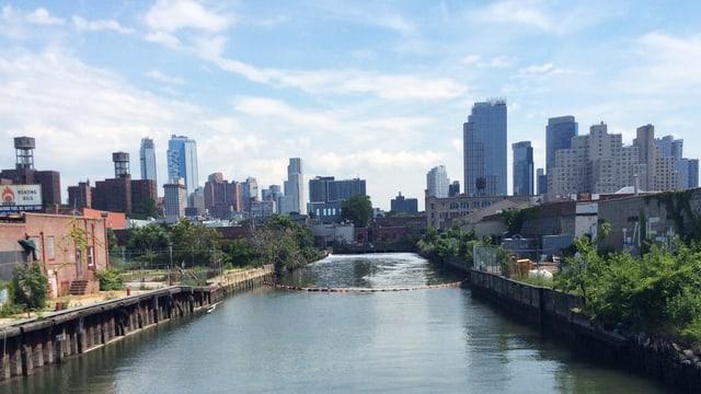 Ein Kanal fliesst duch ein Industriegebiet. Im Hintergrund die Skyline von New York.