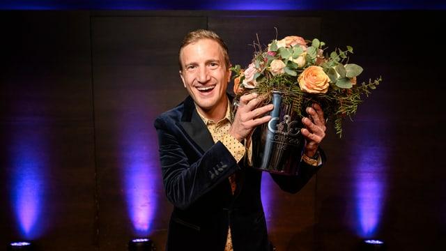 Mann in blauem Jackett mit Blumenstrauss in der linken Hand