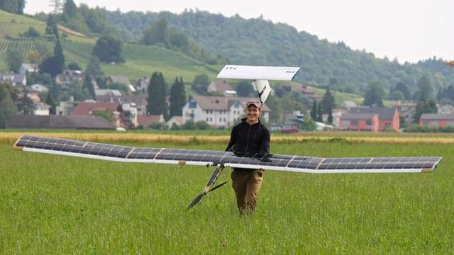 Einer der Forscher halt das grosse Modellflugzeug mit den Solar-Panels auf den Tragflüchen im Arm.
