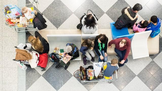 Kunden mit Einkaufswagen in einem Shoppingcenter.