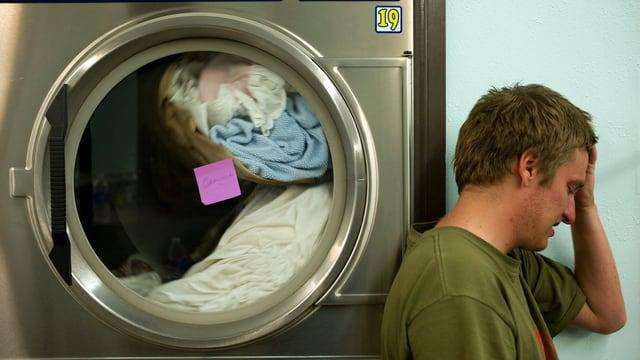 Ein junger Mann lehnt sich an eine öffentliche Waschmaschine und hält sich die Hand an die Stirn.