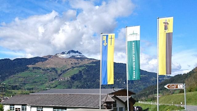 L'entrada al club da golf cun las bandieras dal club, da Schluein e Sagogn. Davostiers il Piz Mundaun.