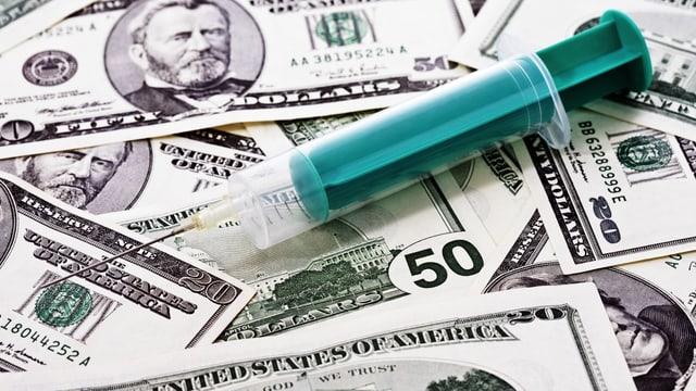 Leere Spritze auf einem Haufen Dollarnoten.