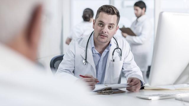 Arzt und Patient sitzen sich an einem Tisch gegenüber.