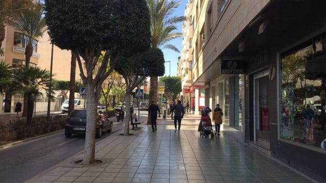 Eine Strasse mit Bäumen an der Seite, im Hintergrund Kinder und Erwachsene.