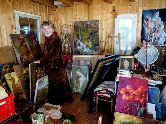 Pfarrer Sieber steht zwischen Bildern in seinem Atelier.