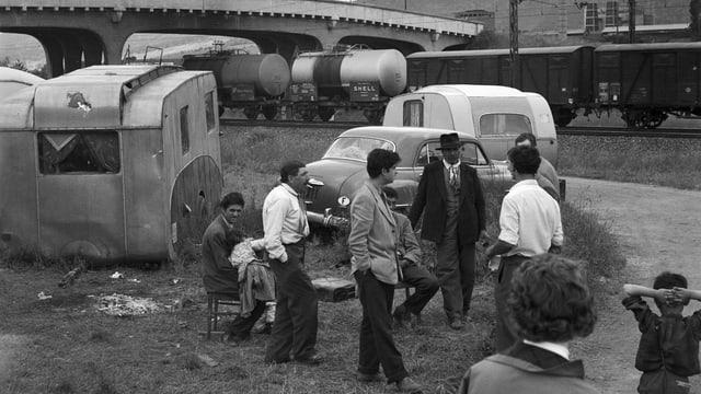 Wohnwagen und eine Gruppe von Männern stehen neben Gleisen.