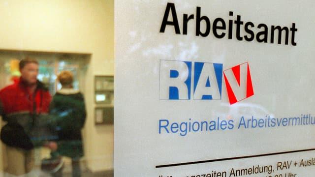 Schild: Arbeitsamt beim RAV, im Hintergrund Stellensuchende am Schalter