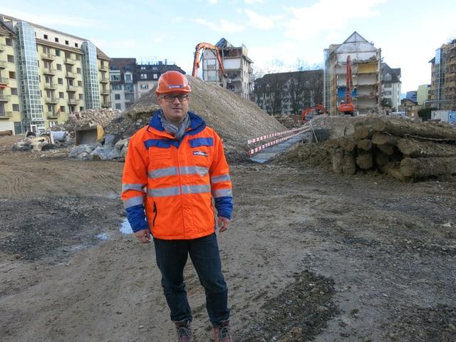 Ein Mann in oranger Leuchtweste und mit Helm auf einer Baustelle.
