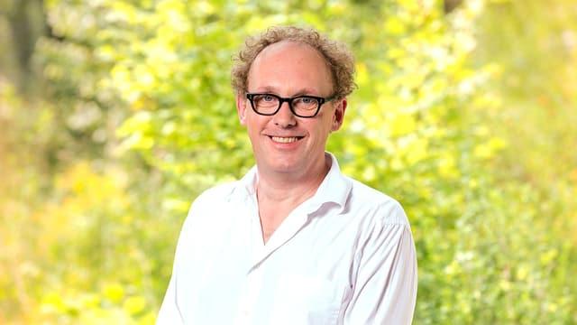 Florian Hauser vor gründem Hintergrund, er trägt eine schwarze Brille.