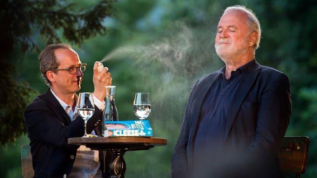 zwei Männer, der eine sprayt den andern mit Mückenspray ein