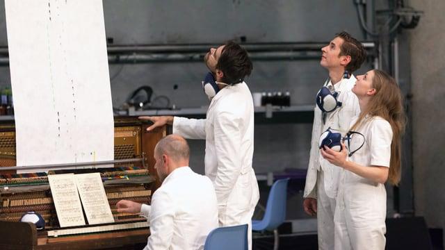 Vier Menschen in weissen Anzügen: Drei stehen und blicken in die Höhe, einer sitzt am Klavier.