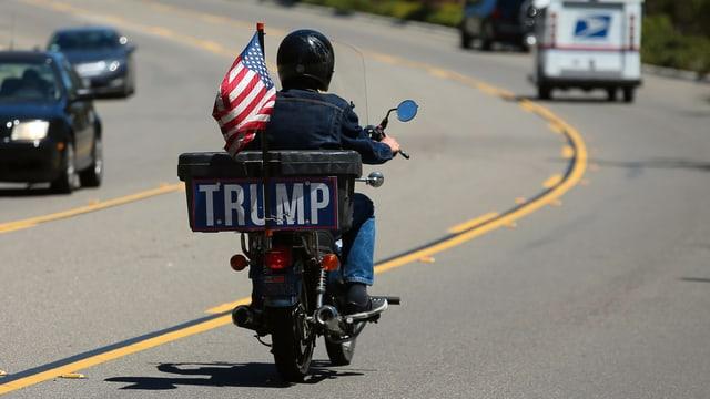 Ein Mann sitzt auf einem Motorrad mit der Aufschrift Trump.