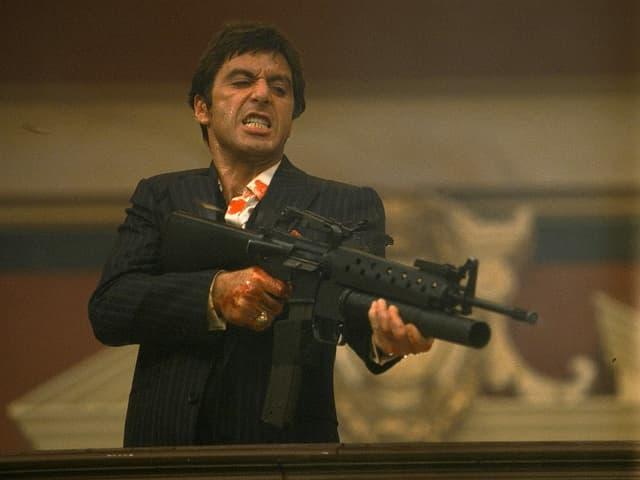 Al Pacino als Tony Montana im Film Scarface. Er trägt einen schwarzen Nadelstreifenanzug. In der Hand hält er ein Maschinengewehr. Er scheint gerade auf jemanden zu schiessen.
